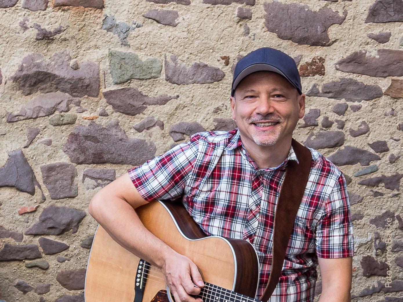Marc Roca mit Guitarre vor Steinwand